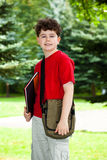Student outdoor. Boy holding notebook standing in park Stock Images
