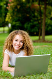 Student Outside. An attractive female student working on laptop in the park stock image