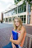 Student Outside of School. Happy female student standing outside of school holding her books. Vertically framed photo Stock Images