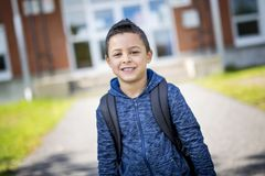 Student outside school standing smiling Stock Image