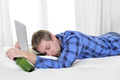 Student overworked asleep on computer holding beer bottle Stock Images