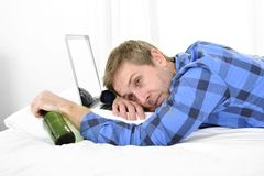 Student overworked asleep on computer holding beer bottle Royalty Free Stock Photography