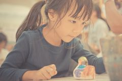 Student is painting doll in art classroom. Student is painting a doll in art classroom royalty free stock images