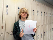 Student with A+  Paper. Image of a student standing next to lockers showing off an A+ paper Stock Image