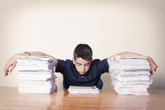 Student with the papers stacked. Student at the school table with the papers stacked stock image