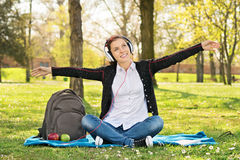 Student in a park with arms outstretched as if she's flying Royalty Free Stock Images