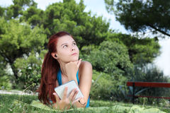 Student in park with digital book and headphones Royalty Free Stock Photos