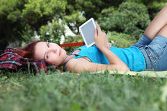 Student in park with digital book and headphones Royalty Free Stock Photo