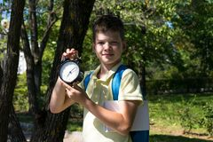 Student in the park keeps an alarm clock, time back to school, holidays are over. Student in the park keeps  an alarm clock, time back to school, holidays are royalty free stock images