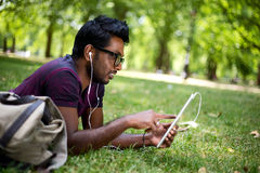 Student in the park. Using his tablet computer Stock Image