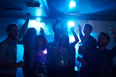 Student party in club. Happy students celebrating graduation in night club, dancing in club smoke with alcohol cocktails beside DJ booth and having fun Stock Images