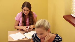 Student passing a note to her classmate Royalty Free Stock Image