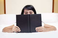 Student peeking from behind the book Royalty Free Stock Photos