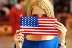 Student peeking behind flag of USA Royalty Free Stock Photography