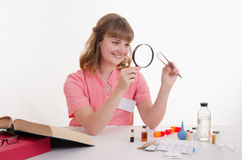 Student pharmacist considers the pill under magnifying glass Royalty Free Stock Images