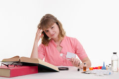 Student Pharmacist delves into directory, tweezers in hand with a tablet Royalty Free Stock Photos