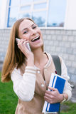 Student with phone and laughing. Student talking on phone and laughing stock photography
