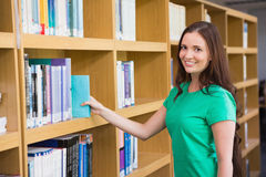 Student picking a book from shelf in library Royalty Free Stock Photo