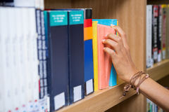 Student picking a book from shelf in library Royalty Free Stock Photos