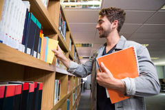 Student picking a book from shelf in library Stock Photos
