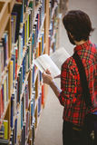 Student picking a book from shelf in library Stock Images