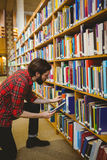 Student picking a book from shelf in library Stock Photo