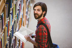 Student picking a book from shelf in library Royalty Free Stock Photography