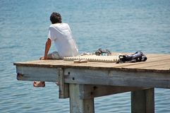 Student on pier. Young male on boardwalk looking at horizon Royalty Free Stock Image