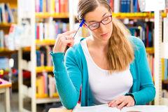 Student with pile of books learning in library Stock Photography