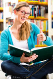 Student with pile of books learning in library Stock Photo
