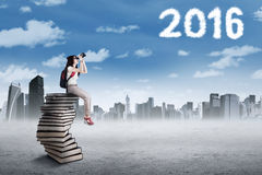 Student on the pile of books looking at numbers 2016 Royalty Free Stock Photography