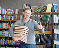 Student with pile books showing thumbs up in college library.  Royalty Free Stock Photography