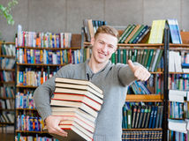 Student with pile books showing thumbs up in college library.  Stock Image