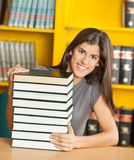 Student With Piled Books Sitting At Table In. Portrait of happy female student with piled books sitting at table in university library Stock Photo