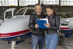 Student Pilot and Instructor Going Through a Pre-Flight Pilot Checklist. Flight instructor talking to female trainee pilot. Beautiful young women pilot holding royalty free stock image