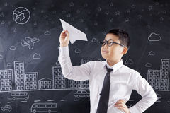 Student playing paper plane in class. Cute schoolboy playing a paper plane in the classroom with a city picture on the chalkboard Royalty Free Stock Photography