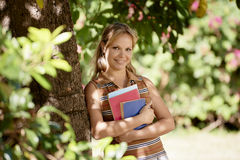 Student portrait at school, happy young woman with university bo Stock Images