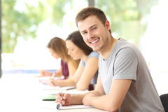 Student posing in a classroom looking at you. Happy student boy posing in a classroom looking at you Royalty Free Stock Photo
