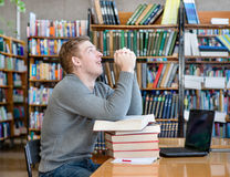 Student prays before examination in a library Stock Photo