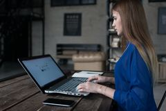 Student preparing for classes surfing the internet on her laptop sitting at table in trendy cafe.  stock image