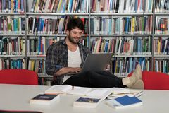Male Student Typing on Laptop in the University Library. Student Preparing Exam and Learning Lessons in School Library - Making Research on Laptop and Browse Stock Photography