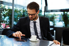 A student preparing for the exam. Portrait of smart and handsome businessman using a digital tablet while sitting at a table in coffee shop, business and royalty free stock photo
