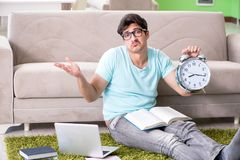 The student preparing for university exams at home in time management concept. Student preparing for university exams at home in time management concept stock photography