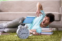 The student preparing for university exams at home in time management concept. Student preparing for university exams at home in time management concept royalty free stock image