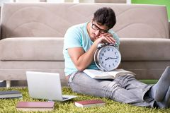 The student preparing for university exams at home in time management concept. Student preparing for university exams at home in time management concept royalty free stock photography