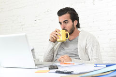 Student preparing university project or hipster style freelancer businessman working with laptop. Young attractive student preparing university project drinking Royalty Free Stock Photography