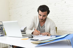 Student preparing university project or hipster style freelancer businessman working with laptop. Young attractive student preparing university project writing Royalty Free Stock Image