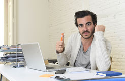 Student preparing university project or hipster style freelancer businessman working with laptop. Young happy attractive student preparing university project or Royalty Free Stock Image