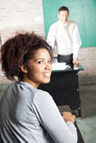 Student With Professor Standing In Background At. Portrait of happy female student with professor standing in background at classroom Royalty Free Stock Photography
