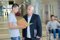 Student and professor talking in hallway Stock Photography